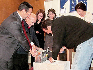Left to right: Mayor Joseph Curtatone, David Pignone and Sal Querusio work to open a time capsule removed from the cornerstone of the former Saint Polycarp School. Looking on are Ursula Salerno, Meridith Levy and Camille Long. ~Photo by Elizabeth Sheeran