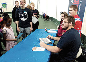 "New England Patriots Center Ryan Wendell signed autographs read to kids at ""Read by the River"" Carnival at the Tufts Gancher Center last Sunday. ~Photo by Terence Clarey"