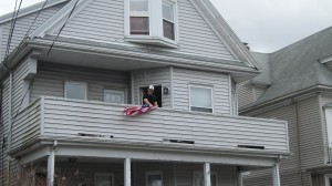 Neighbors of Officer Collier drape a flag off their porch Friday. ~Photo by Bobbie Toner