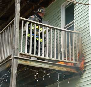 Firefighter Tom Ross works to extinguish flames spreading in a rear wall of 68-70 Holland Street on April 16. ~Photo by Somerville Fire Department.