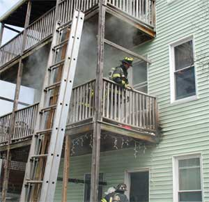 A ladder is raised as smoke envelopes Firefighter Mike Finnegan working on a rear porch of 68-70 Holland St.