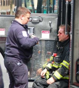 Firefighter Tom Ross is treated for a facial laceration by an EMT from Cataldo Ambulance during the fire.  ~Photo by Somerville Fire Department.